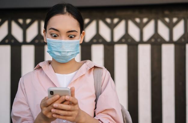 Mulher asiática assustada com máscara médica segurando um telefone celular, lendo notícias chocantes