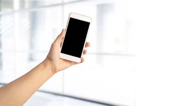 Mulher asiática ativa segurando um telefone celular para se comunicar sobre o trabalho em um escritório moderno