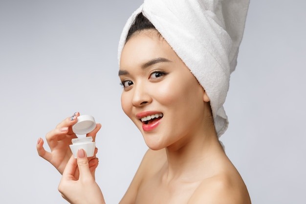 Mulher asiática atraente aplicar creme na pele dela