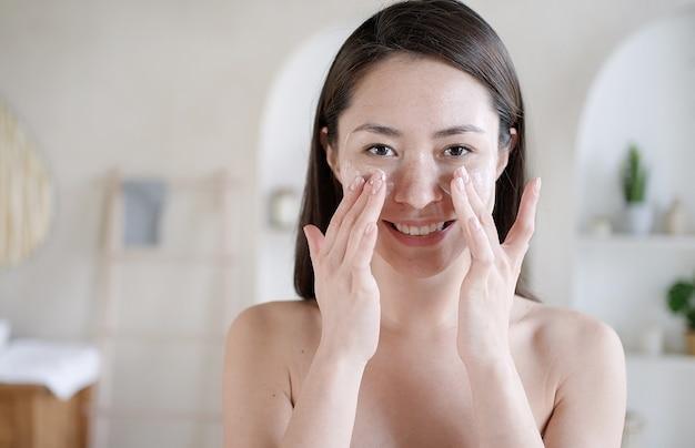 Mulher asiática atraente aplicar creme para a pele no rosto olhar no espelho do banheiro em casa jovem mestiça feliz colocar creme facial hidratante para levantamento de pele e conceito de tratamento corporal saudável