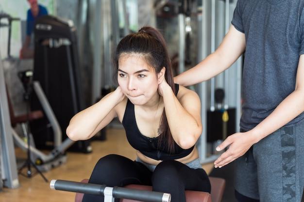 Mulher asiática atraente aptidão fazendo exercício com seu treinador.