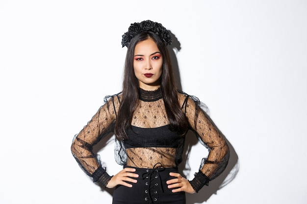 Mulher asiática atraente com fantasia de halloween, parecendo decepcionada e cética. mulher em vestido de renda preta e grinalda parecendo arrogante, doce ou travessura em roupa de bruxa, fundo branco de pé.