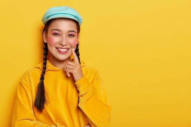 Mulher asiática atraente com maquiagem rosa, mantém o dedo indicador na bochecha, pondera sobre uma boa ideia, usa moletom casual de veludo amarelo com capuz, sorri gentilmente