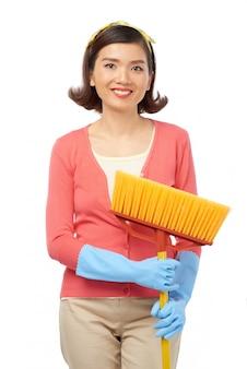Mulher asiática atraente com vassoura