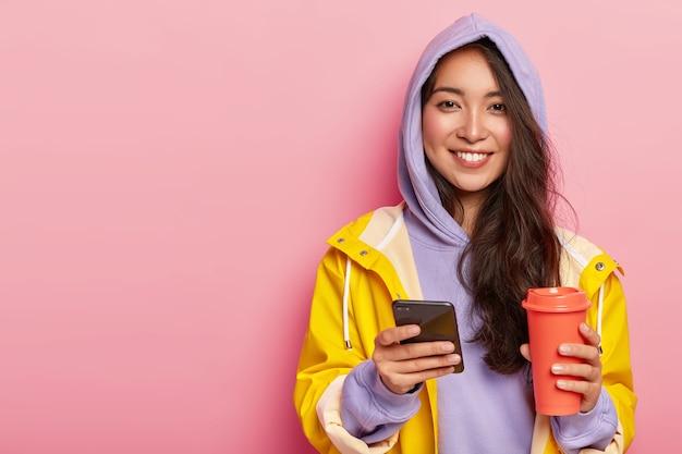 Mulher asiática atraente e encantada usa roupas casuais, capa de chuva, manda mensagem pelo celular, bebe bebida aromática da garrafa térmica