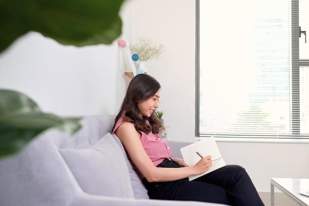 Mulher asiática atraente escrevendo o diário no caderno ao lado da janela durante a manhã no fim de semana