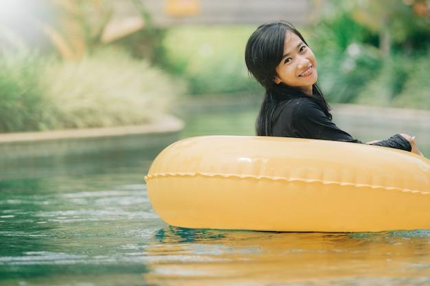 Mulher asiática atraente relaxante na piscina do rio