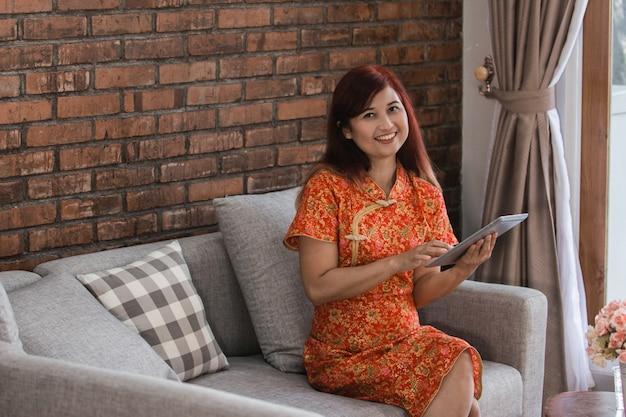 Mulher asiática atraente usando vestido vermelho sentado segurando o tablet
