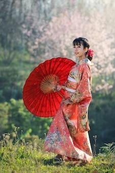 Mulher asiática atraente vestindo quimono japonês tradicional com guarda-chuva vermelho