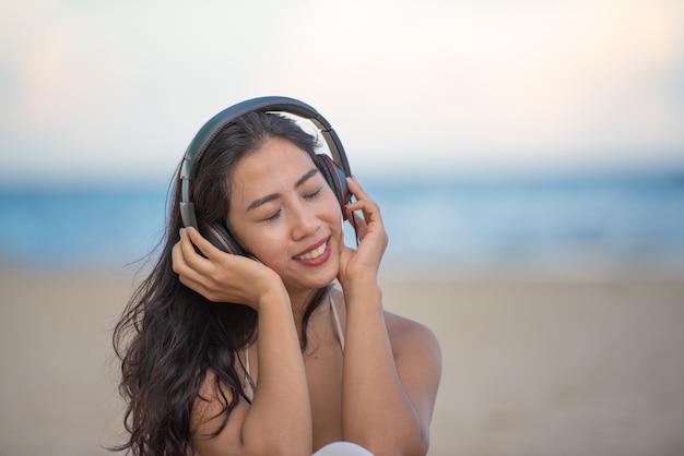 Mulher asiática atrativa de sorriso com felicidade e que aprecia na praia