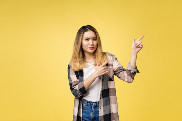 Mulher asiática atrativa nova que aponta ao dedo com emoção infeliz.
