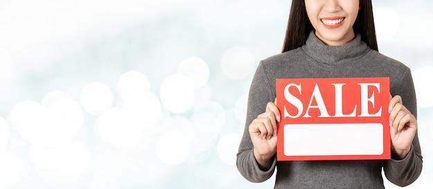 Mulher asiática atrativa nova que guarda o cartão da tabuleta da venda que mostra para o preço