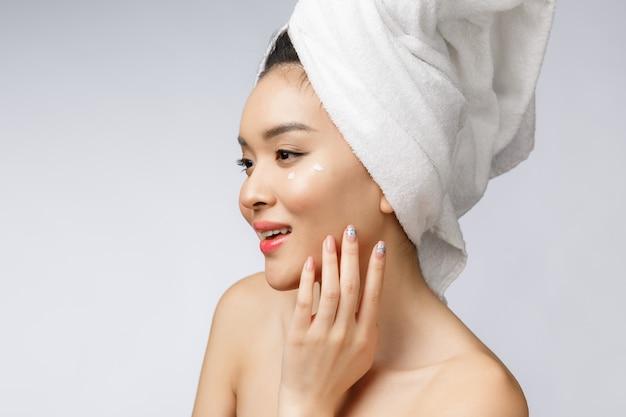 Mulher asiática atrativa que aplica o creme em sua pele, isolado no branco.