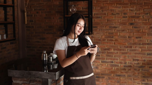 Mulher asiática barista sorrindo e segurando o telefone. verifique o pedido online do cliente.