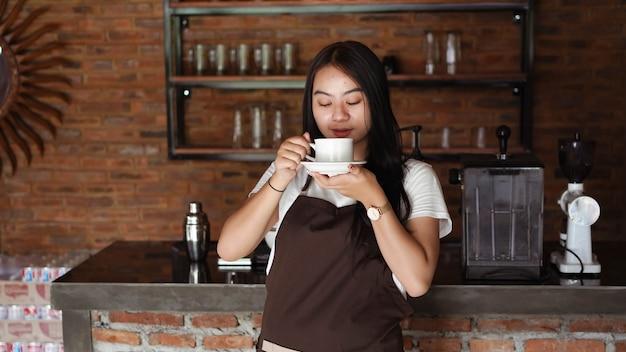 Mulher asiática barista sorrindo no balcão da cafeteria. mulher barista segurando uma xícara de café no café