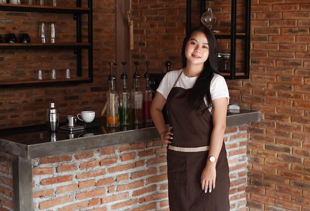 Mulher asiática barista sorrindo para a câmera do café
