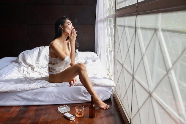 Mulher asiática bêbada em lingerie branca, bebendo e fumando enquanto segura a garrafa de álcool e sentado na cama no quarto