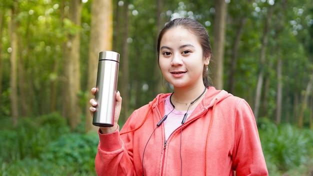 Mulher asiática bebendo água após exercício em fundo de floresta verde