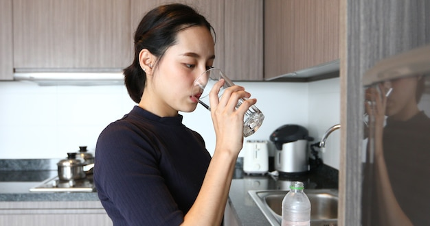 Mulher asiática bebendo água em vidro na cozinha