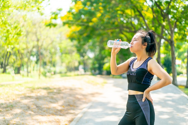Mulher asiática bebendo água no sportwear