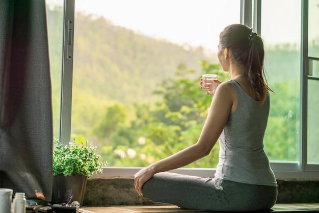 Mulher asiática beber água ao lado da janela