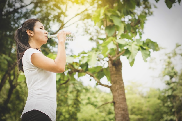 Mulher asiática beber água fresca da garrafa no parque