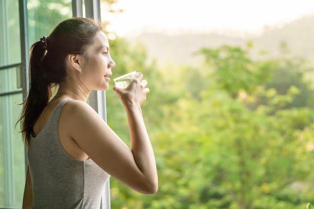 Mulher asiática beber água limpa de manhã