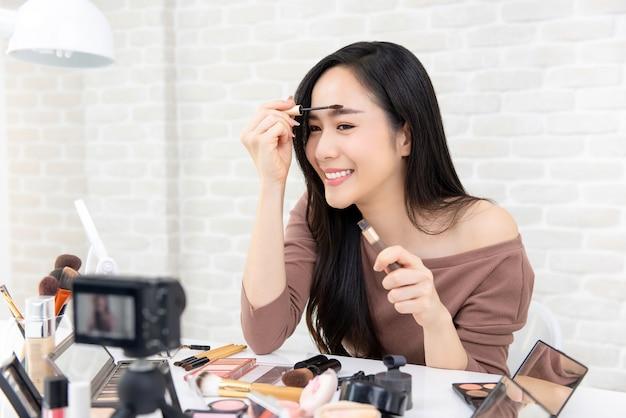 Mulher asiática beleza vlogger fazendo maquiagem cosmética tutorial vídeo