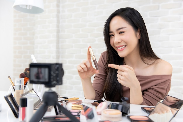 Mulher asiática beleza vlogger gravação maquiagem revisão