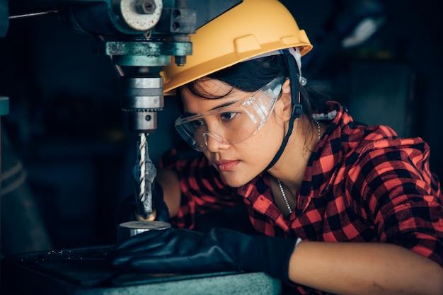 Mulher asiática beuatiful trabalhando com máquina no engenheiro de fábrica e conceito de mulher trabalhadora ou dia da mulher