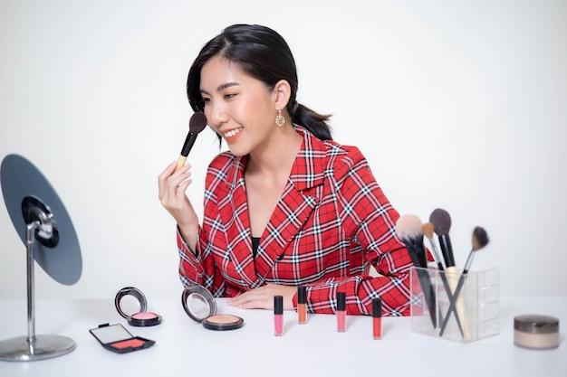 Mulher asiática blogueira de beleza faz maquiagem, analisa produtos de beleza para videoblog