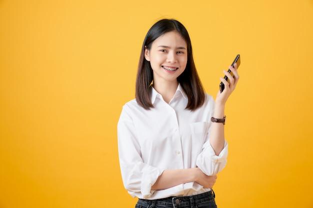 Mulher asiática bonita alegre segurando o smartphone em amarelo claro.