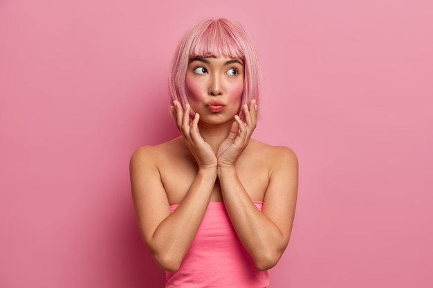 Mulher asiática bonita com bochechas ruge, mantém os lábios dobrados, as mãos perto do rosto, tem expressão pensativa, cabelo rosa, vestida de top