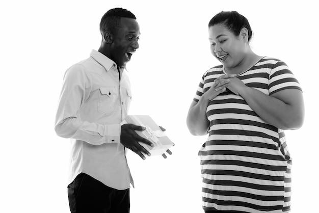 Mulher asiática bonita com excesso de peso e um jovem africano juntos como um casal em preto e branco