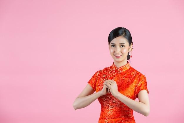 Mulher asiática bonita com gesto de parabéns no ano novo chinês