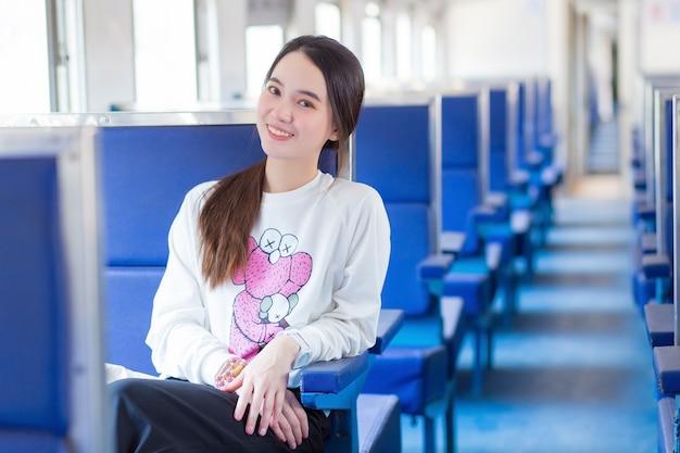 Mulher asiática bonita com jaleco branco sentar na cadeira durante a viagem de trem.