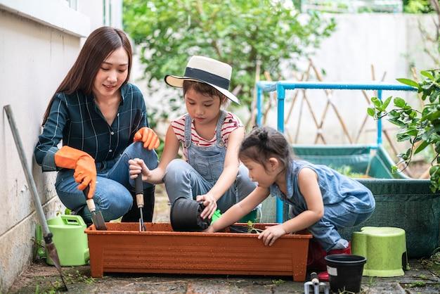 Mulher asiática bonita com sua filha fazendo jardinagem em sua horta doméstica