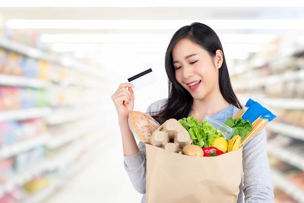 Mulher asiática bonita compras mantimentos com cartão de crédito no supermercado