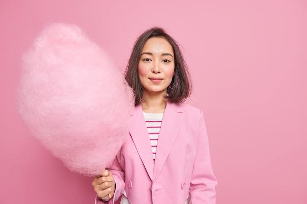 Mulher asiática bonita contém algodão doce rosa adoçado, vestido com roupas formais, passa o feriado com crianças, come sobremesa doce de alto teor calórico isolada sobre uma parede rosada. conceito de estilo de vida
