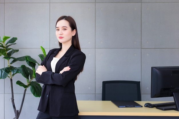 Mulher asiática bonita de negócios bem-sucedida que tem cabelo comprido e usa um terno formal preto com camisa azul