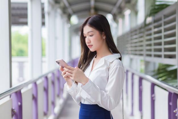 Mulher asiática bonita de negócios parada no viaduto do skytrain na cidade enquanto usa seu smartphone