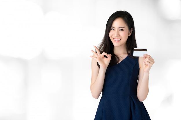 Mulher asiática bonita de sorriso nova que mostra o cartão de crédito com gesto do okey