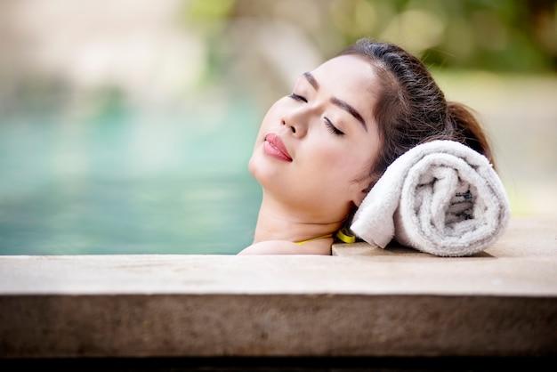 Mulher asiática bonita deitada na beira da piscina