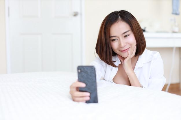 Mulher asiática bonita do close up, cabelo curto na camisa branca usando a chamada video ou o autorretrato do telefone celular.