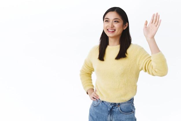 Mulher asiática bonita e amigável dizendo olá, sorrindo feliz e acenando com a mão para a esquerda, vendo amigo, líder da equipe fazendo gesto de despedida após um trabalho produtivo, sentindo-se satisfeito e encantado