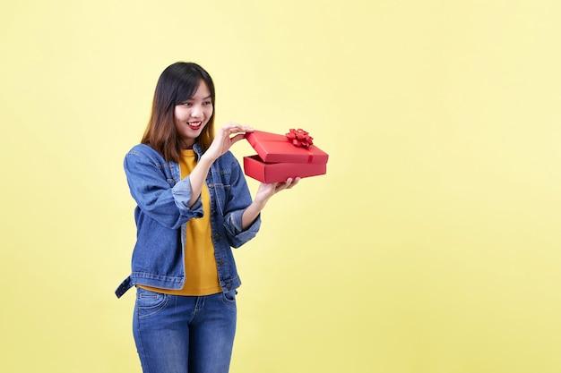 Mulher asiática bonita e animada segurando uma caixa de presente vermelha