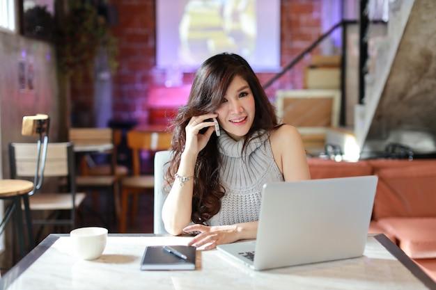 Mulher asiática bonita e atraente, cabelos longos, em vestido casual cinza trabalhando