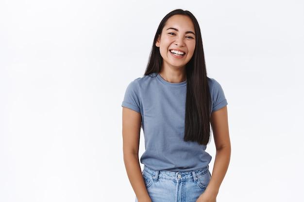 Mulher asiática bonita e entusiasmada rindo alto, sorrindo e olhando a câmera se divertindo, se divertindo, comparecendo a um show engraçado, rindo sobre a parede branca