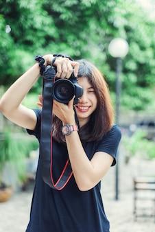 Mulher asiática bonita e feliz que guarda a câmera no jardim.