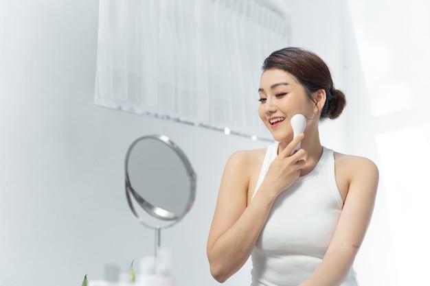 Mulher asiática bonita e mão segurando massagem facial elétrica isolada na parede branca